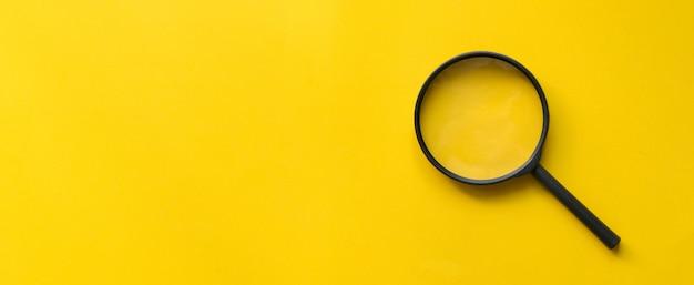 黄色の背景に拡大鏡ガラスを閉じる