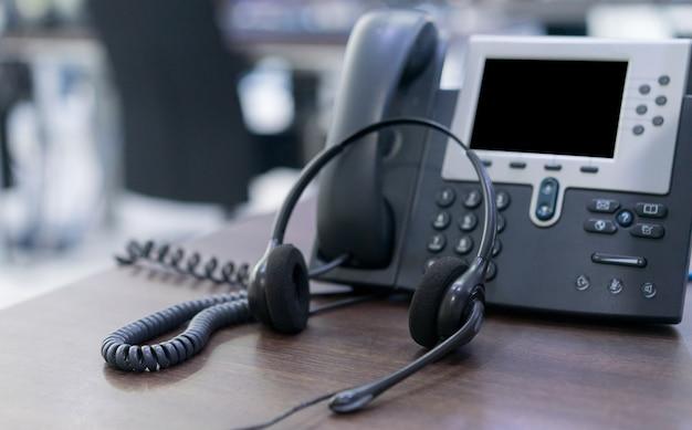手術室の事務机でコピースペースの背景を持つヘッドセットと電話デバイス