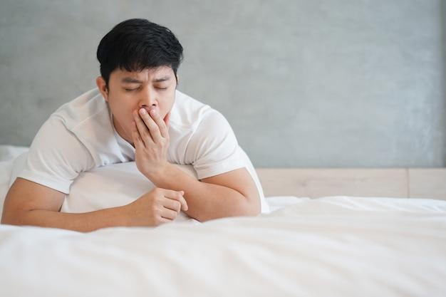 アジア人の男性が眠いと休暇日に寝室であくびを閉じる