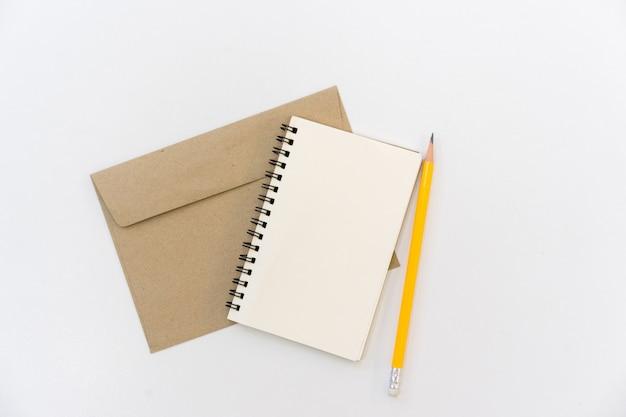 白いテーブル背景に黄色の鉛筆で黄褐色の手紙に空白のメモ帳を閉じる