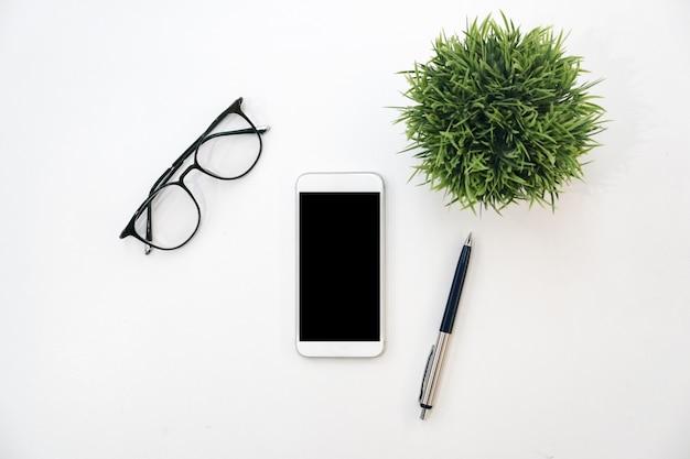 Вид сверху макета смартфона, стекла, ручки и растений на фоне белого цвета