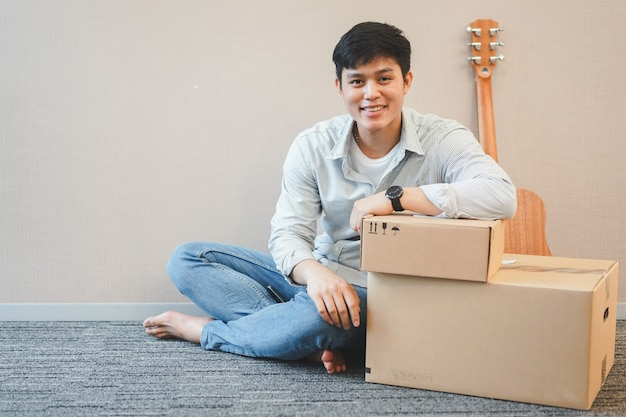 ボックスとギターで坐っている人は新しい住居、千年紀と家の概念で装飾を準備します。