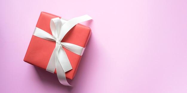 ピンク色の背景上の白いリボンとギフトボックス