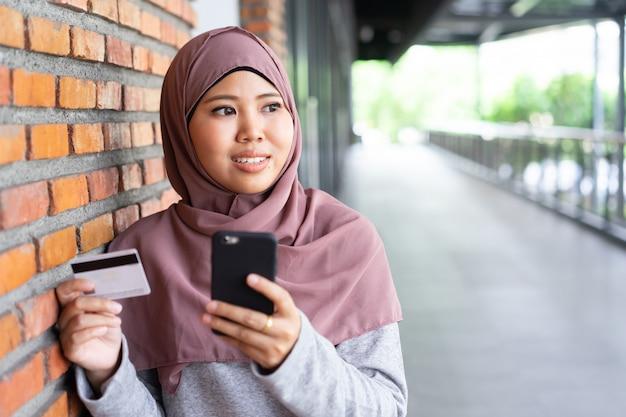イスラム教徒の女性の手はリラックスした時間に買い物に携帯電話とクレジットカードを保持します。