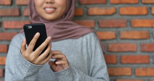 Азиатская мусульманская женщина, держащая смартфон