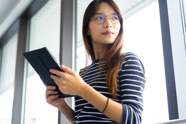 Молодая коммерсантка смотря вне окно с зрением и держа концепцию терминала аэропорта таблетки