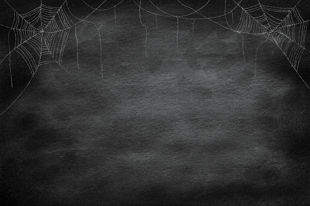 ハロウィーンの夜のパーティーのためのレトロなビンテージ黒板背景にコーナーでクモの巣のグループを描く