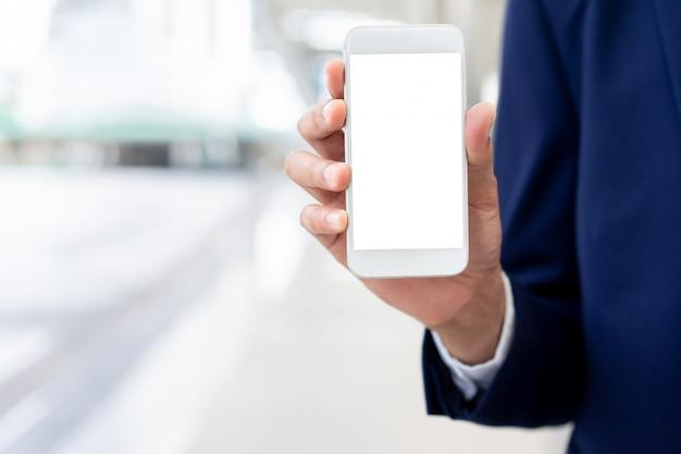 空白の白い画面を持つスマートフォンを持っているビジネスマン手