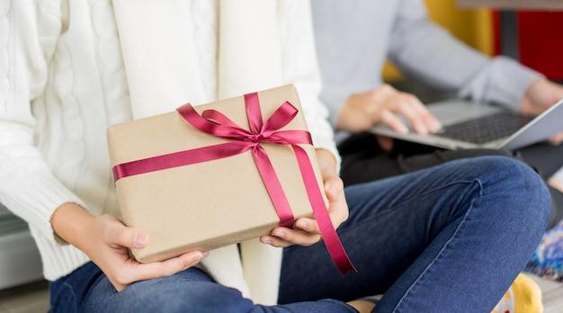 ギフトを保持している女性と家のリビングルームで一緒に友達と一緒に座るパーティーメリークリスマスの準備