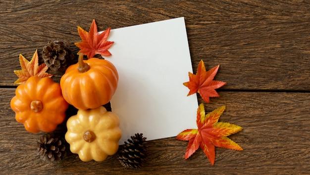 カボチャ、松ぼっくり、カエデのグループと白い空白の紙はヴィンテージの茶色の木のテーブルに残します