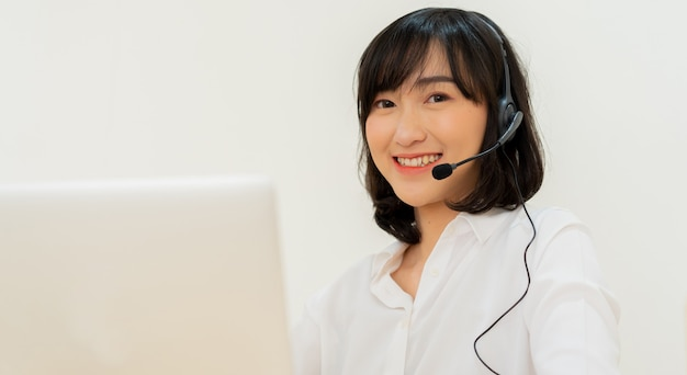 コールセンターの従業員の若い日本人女性が手術室に座っているヘッドセットデバイスを着用します。
