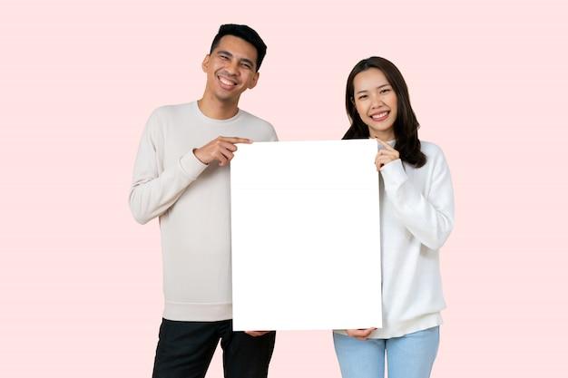 恋人のアジア人はバレンタインの日にピンク色の背景に分離された白いモックアップボードを一緒に保持します。