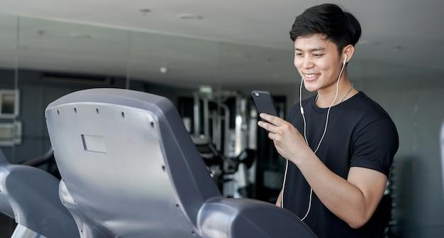 トレッドミルマシンで歩きながら再生するためのスマートフォンを保持している男を閉じる