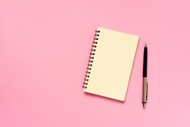 ピンク色の背景概念にペンで空のノートブックのトップビュー