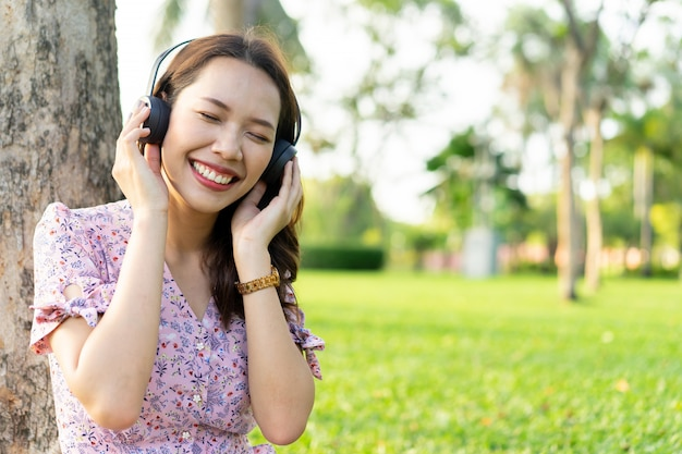 Азиатская красивая женщина слушает музыку в парке
