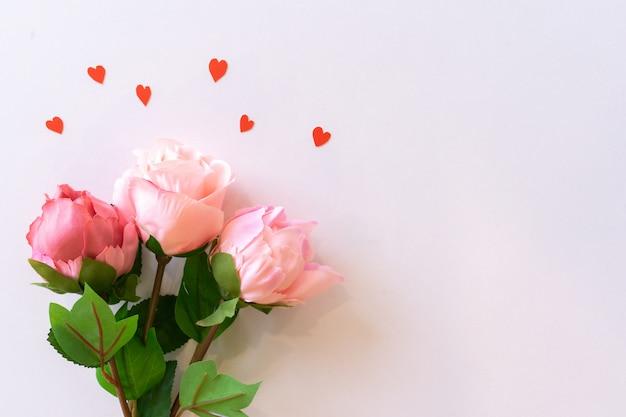 バレンタインと母の日の概念のピンク色の背景にバラとハート形のトップビュー