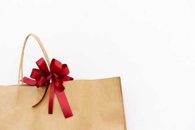 バレンタインの日と母の日の概念のための白い背景に包まれたギフトと赤い弓を閉じる