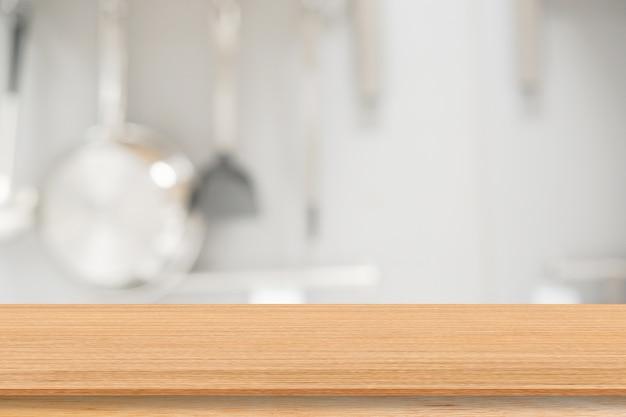 ショー用の調理器具と木製テーブル付きのモダンなキッチン内をぼかし、製品の背景を宣伝