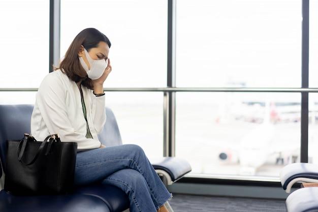 コロナウイルスの概念のための空港のゲートに座っている女性はフェイスマスクと頭痛を感じる女性