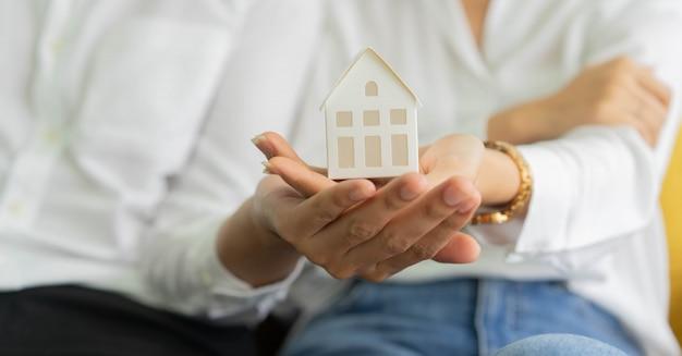 Новая супружеская пара держит модель дома вместе для концепции ипотечного кредита и инвестиций