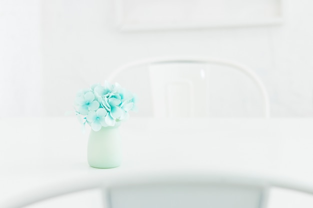美しい白い部屋のテーブルの上の陶製の花瓶の青いアジサイの花。