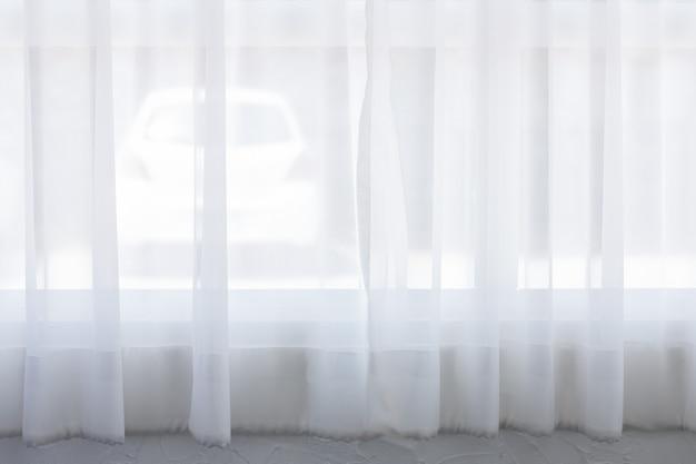 窓の後ろの車には、背景に美しい白いカーテンがあります。朝の光の中。