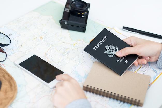 スマートフォンを押す女性の手。オンラインでチケットを購入し、旅行を計画しています。