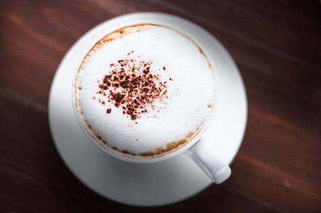 カカオのコーヒー、ダークウッドの背景の上に白いカップでトッピング