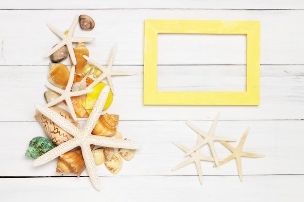 魚の星、海の殻と黄色の木枠は、白い木製の背景に。