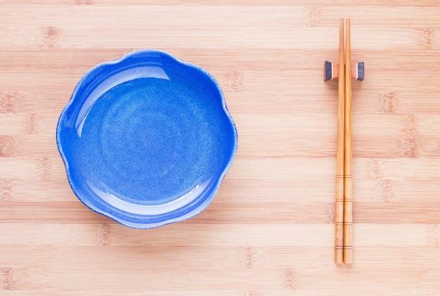 空のセラミックプレートと木製テーブル上の箸のトップビュー。和風。