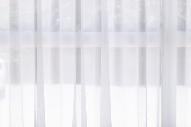 ウィンドウには、背景のための美しい白いカーテンがあります。朝の光の中で。