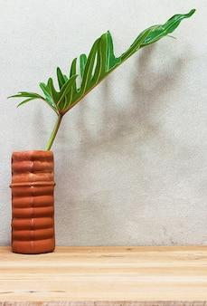 木製のテーブルの上に花瓶の観葉植物。
