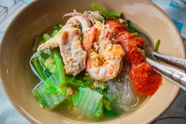 Суки в бульоне смешанные морепродукты с вермишелью и овощами.