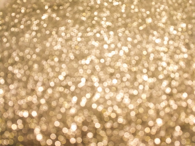 明るく輝くボケの背景。イエローゴールド - 光沢のあるテクスチャからのぼやけた照明。