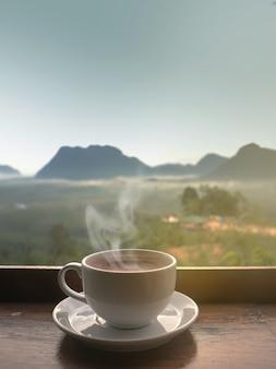 ぼやけた山の風景の上の日光と朝の木製のテーブルに白いセラミックコーヒーカップ