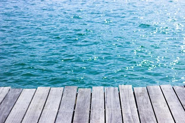 青い海の背景を持つ木製のテーブルトップ。