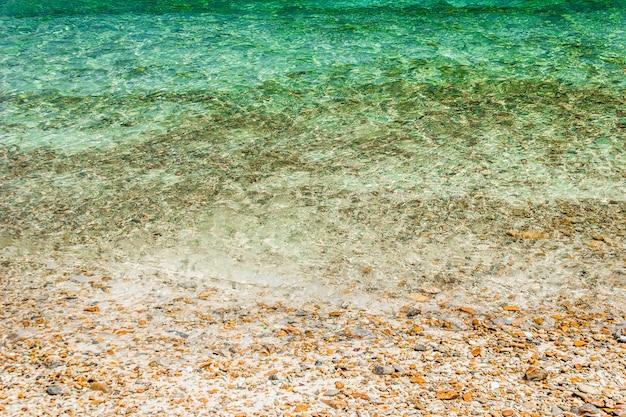 小石や砂浜の水の泡で柔らかい波。