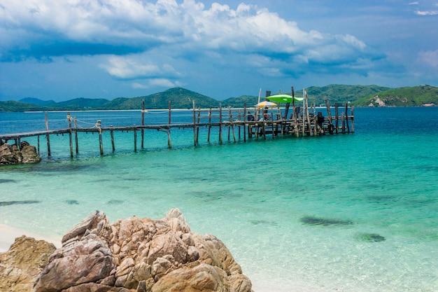 Деревянный мост на пляже с водой и голубым небом. ко кхам паттайя