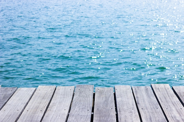 青い海の背景を持つ木製テーブルトップ。