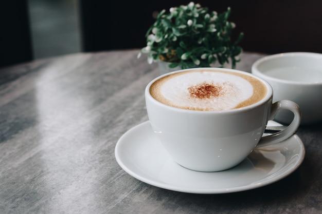 大理石のテーブルの上の緑の葉とホットコーヒーと花瓶