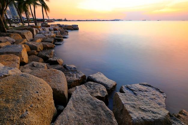 タイの海で石の海岸の美しい色鮮やかな夕焼け。