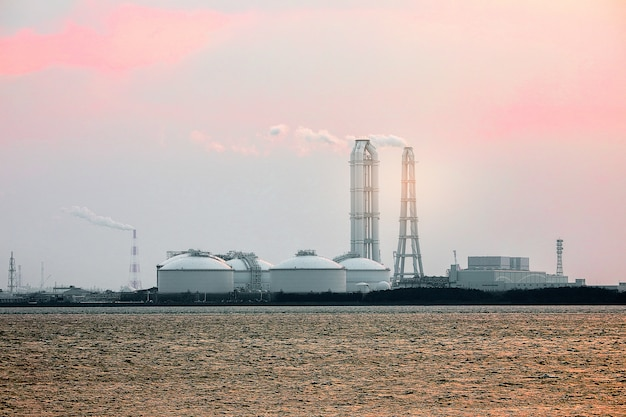 日没時間、産業および環境の概念で煙と海の工業団地区域または工場。