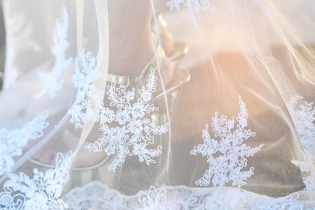 女性の足と結婚式の靴の中でクローズアップのウェディングドレス。結婚式のコンセプトです。