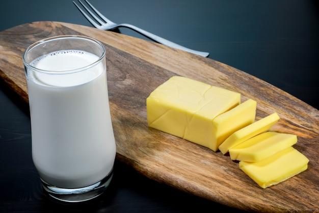 ガラスの新鮮な牛乳で木の板にクローズアップスライスチーズ。