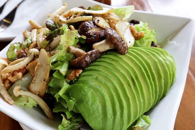 健康的なビーガンランチボウルを閉じます。マッシュルーム、アボカド、グリーンオーク、レッドオーク、ピーカンナッツ、木製テーブルのヘルシーソース付き。食品