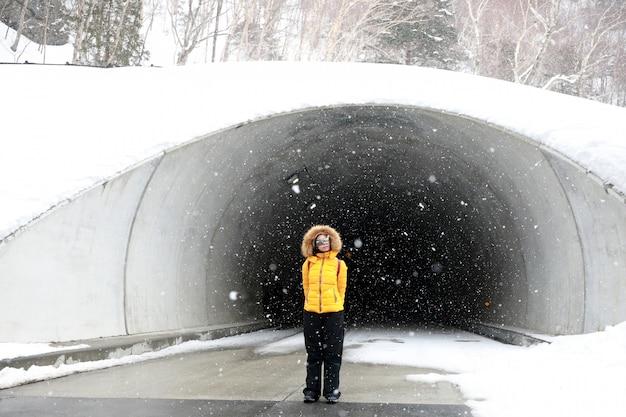 雪が降るトンネルの女性