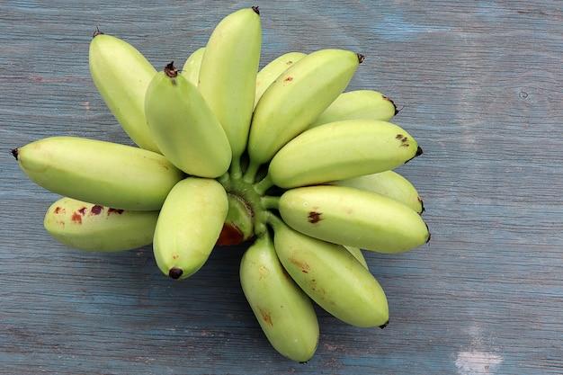 Вид сверху сырой вид банана на фоне синего деревянного стола. фрукты здоровые концепции.
