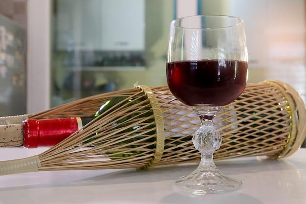 木製のバスケットにワインのボトルとカウンターバーのワイングラスに赤ワイン。