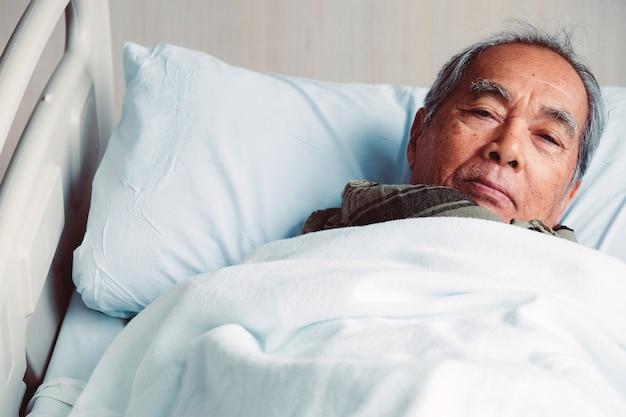 病院のベッドで高齢の患者