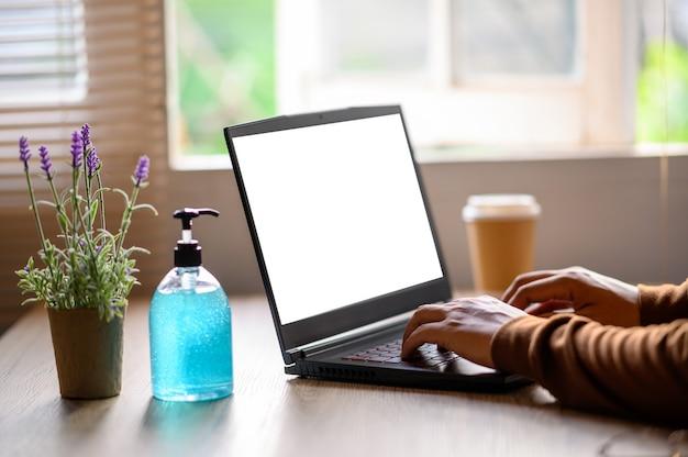 伝染病ウイルスの間に自宅で仕事をするための机の上のラップトップ。